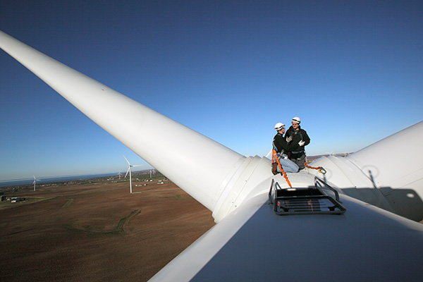 Two technicians servicing a wind power turbine